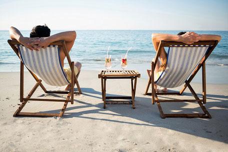 Zwei Urlauber sitzen mit nackten Füßen im Ostseesand, entspannt im Liegestuhl, dazwischen ein kleines Tischchen mit einem Drink