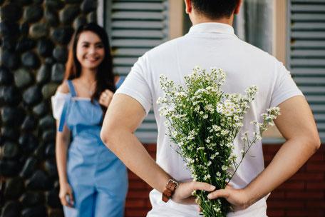 Mann mit Blumenstrauß, der seine Traumfrau überrascht