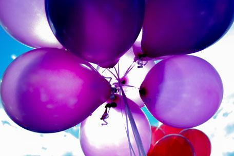 lila Luftballons schweben unter blauem Himmel