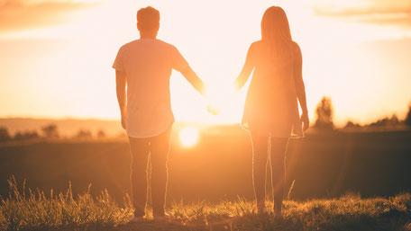 Pärchen läuft händchenhaltend in den Sonnenuntergang