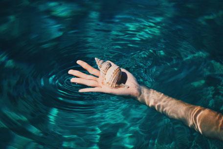 Arm liegt in klarem blauen und kaltem Wasser.