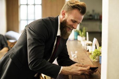 Ein Mitarbeiter liest eine SMS auf dem Smartphone