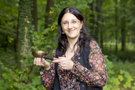 Christina M. Uhlmann mit Klangschale im Wald