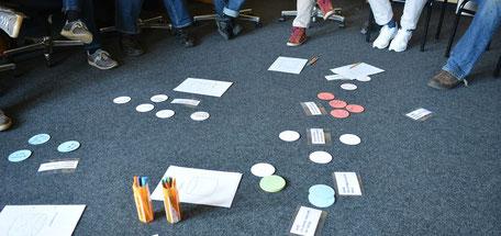 Menschen sitzen während eines Seminars im Kreis und haben auf dem Teppich rundes buntes Papier und Stifte verteilt