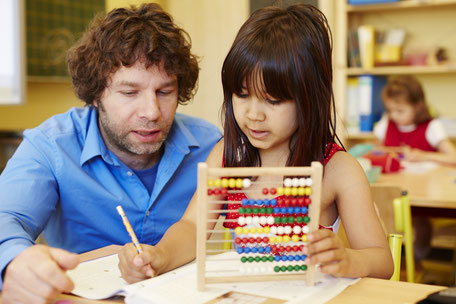 Foto von Lehrer und Kind mit Rechenschieber