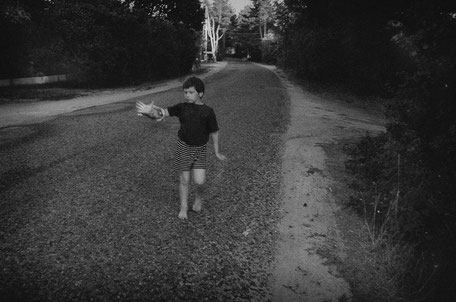 LATVIA / From the book 'Auftakt'. Boy walking barefoot with his hand in front of his face, 2008