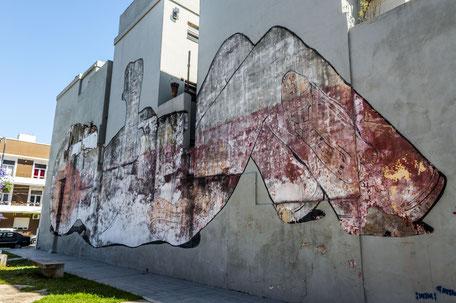 Der schon etwas verplasste Gigant daneben stammt aus dem Pinsel von Blu. Blu gilt als, der Künstler des Muralismus und lebt unter verborgener Identität in Bologna.
