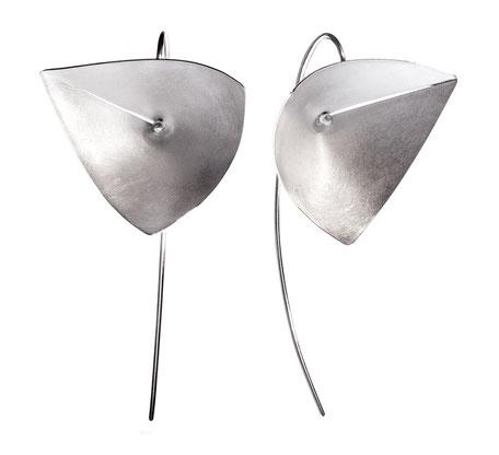 Die hochwertigen, stilvollen Ohrhänger VELA aus Silber ziehen die Blicke auf sich. Ihre klare, außergewöhnliche Gestalt erinnert an ein geschwungenes, unwiderstehlich schimmerndes Segel. Sie fühlen sich außergewöhnlich & unbeschwert, VELA ist federleicht