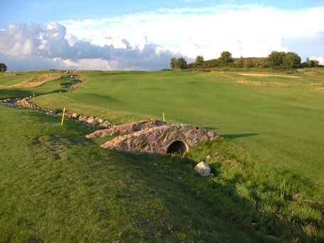 Golfplatz mit alter kleiner Steinbrücke im Vordergrund
