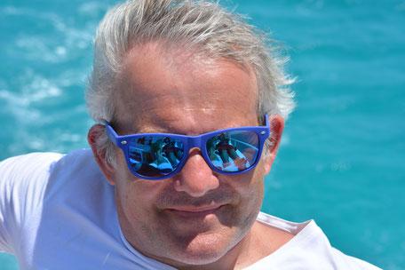 Martin Rotter mit Sonnenbrille. Im Hintergrund türkises Meer.