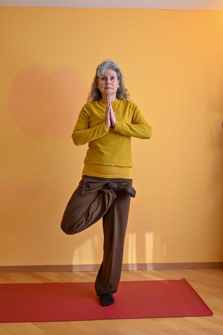 In tādāsana ist die Brustwirbelsäule sanft angehoben. Die Handhaltung vor dem Herzen drückt eine Zentrierung im Herzen aus. Der unsichere Stand auf einem Bein erfordert eine wache, bewusste Abstimmung mit dem äußeren Raum.