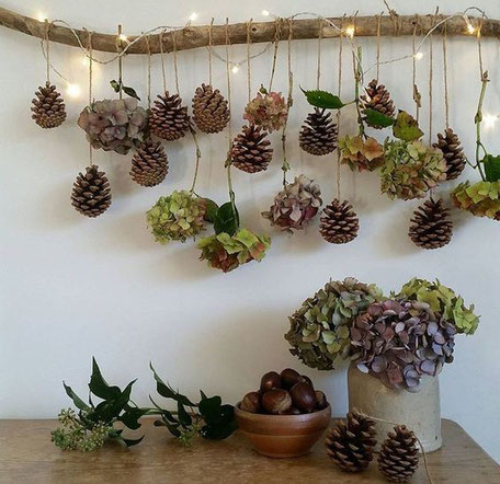10 plus pine cone Christmas decor DIYs, A display of flowers and pine cones with lights image via pinterest