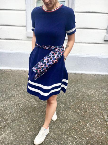 Frau mit blauen Kleid und Schal auf Straße