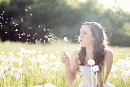 Frau in einer Wiese mit Pusteblume in der Hand