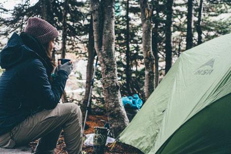 Picknick im Wald mit warmen Tee und Zelt