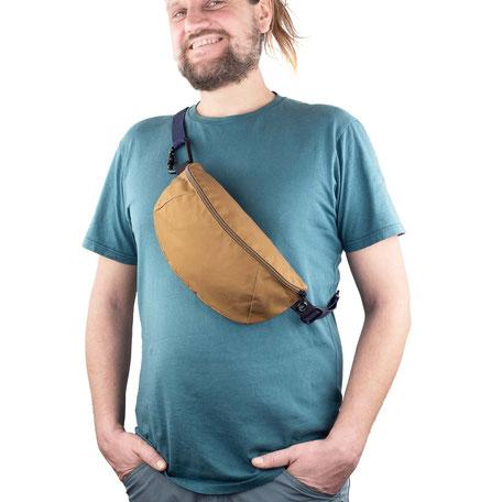 Braune Bauchtasche/Brustbeutel mit schwarzem Karabiner und dunkelblauem Band.