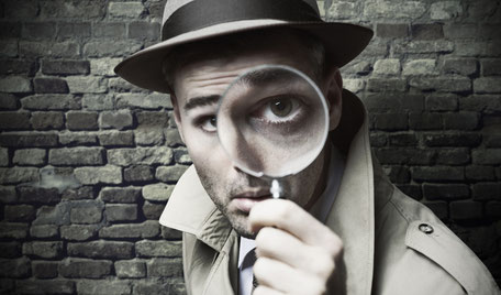 Detektiv schaut durch die Lupe, damit er gut sieht, wie und wo man sich niedrige Zinsen für die Immobilienfinanzierungen, Baudarlehen oder Hypothekenkredite sichert.