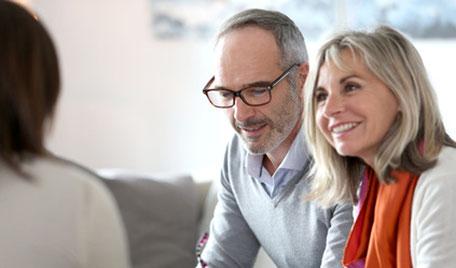 Strahlendes Ehepaar bei der Altersvorsorgeberatung über die Basisrente