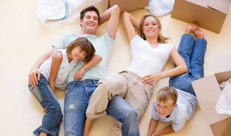 Glückliche Familie auf der Wiese liegend, dank gut geplanter Altersvorsorgeabsicherung mit der Riester-Rente