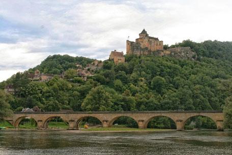 Des rives de la Dordogne, on aperçoit en haut de son éperon rocheux, au milieu des arbres, le château de Castelnaud.