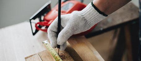 Eine Hand, die ein Stück Holz abmisst und Markierungen setzt