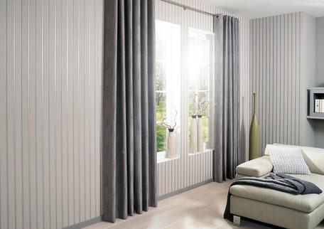 Eine Wand mit weißer Verkleidung und grauen Vorhängen
