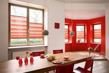 Ein Esszimmer mit roten Plissees als Sonnenschutz vor den Fenstern