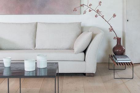 Weißes, gepolstertes Sofa mit Couchtisch und einer Vase