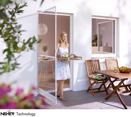 Eine Frau geht durch eine geöffnete Insektenschutztüre auf eine Terasse