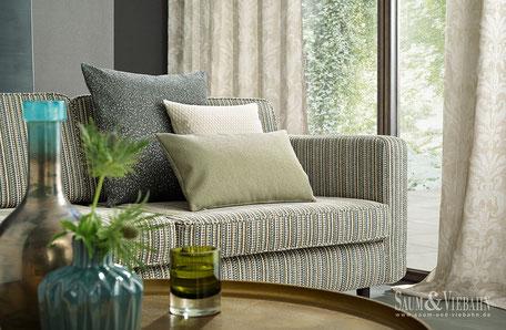 Drei Kissen auf einer mit grünem überzogenen Couch