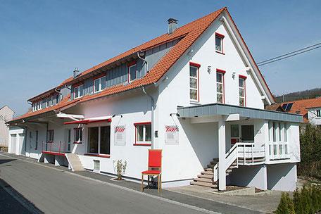 Das Gebäude von Raumausstattung Roser mit roten Akzenten