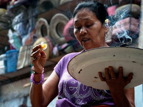 Balinese vrouw die offers brengt aan de Hindoe goden op Bali