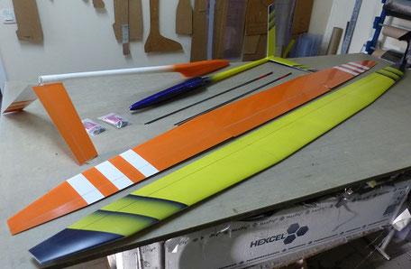 2 miraj Aeromod démontés sur une table, côté intrados un blanc et orange, un jaune et bleu foncé