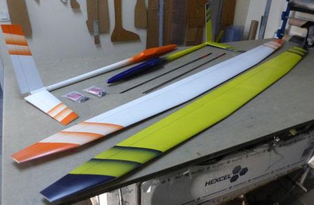 2 miraj Aeromod démontés sur une table, côté extrados un blanc et orange, un jaune et bleu foncé