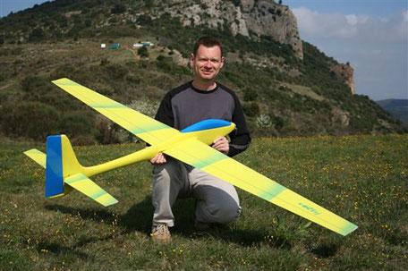 planeur Voltij Aeromod jaune et bleu primaire, porté par un homme