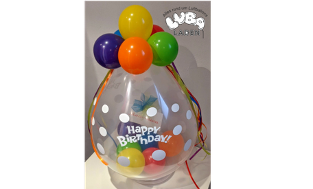 Verpackungsballon aus transparentem Latex mit einer hängenden Motivationskarte und regenbogenfarbene kleine Ballons