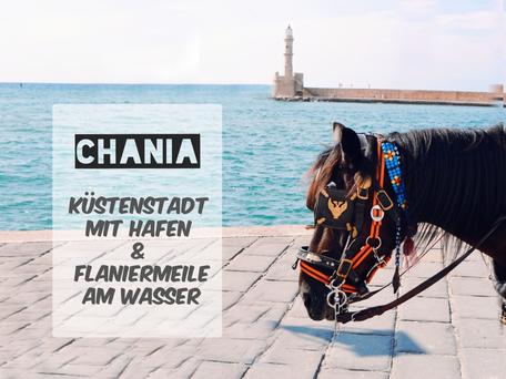 Strandprommenade und ein Pferd mit buntem Zahmzeug und dem Leuchtturm von Chania im Hintergund