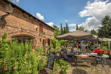 Café im Auenhof und die Kunstgalerie Aagaard im Berliner Stadtteil Hermsdorf. Gemütliche Sitzplätze locken im Garten.