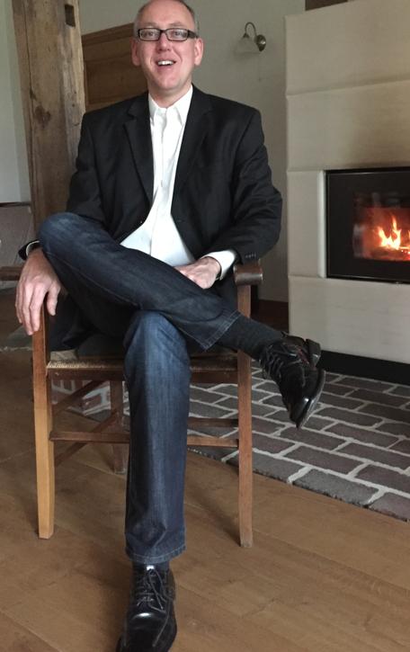 Unternehmensberater Reinhard Vossmann auf einem Stuhl vor dem Kamin