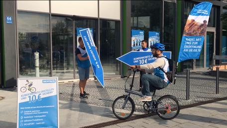 SignSpinner und SignSpeeder auf Fahrrad bei einer Werbekampagne für eine Neueröffnung.