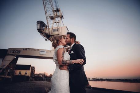 Ein Brautpaar küsst sich in einem Industriehafen.