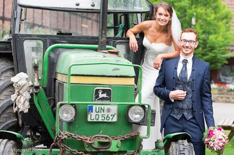 Ein Brautpaar posiert vor einem Traktor.