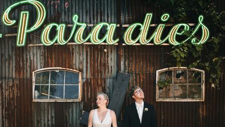 """Ein Brautpaar steht von einem rostigen Schuppen mit der Leuchtschrift """"Paradies""""."""