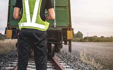 Eine Person steht vor einem Güterzug