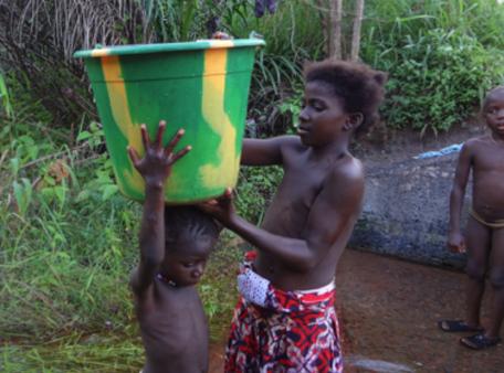 Kinder tragen schwere Wassereimer