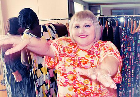 Beth Dito in einem Kussmund-Oversize-Shirt in den Farben creme, rot, orange und pink