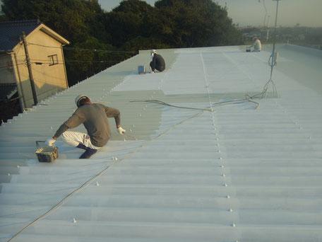 金属折板屋根の中塗りをローラーにて塗装中。パラサーモシリコン遮熱塗料使用