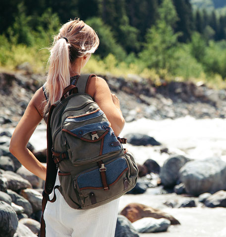 Woman with ponytail and back turned carrying a backpack hiking in a valley with a river and mountains in the background.