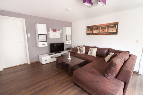 Wohnzimmer mit großer Couch und TV