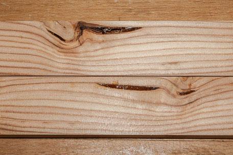 Bretter mit Ast- und Harzeinschlüssen, die die Holzeigenschaften beeinflussen